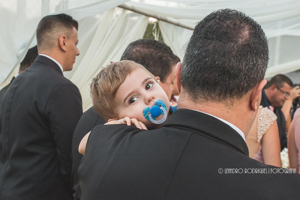 Criança no colo do padrinho, com chupeta na boca, olhando para trás