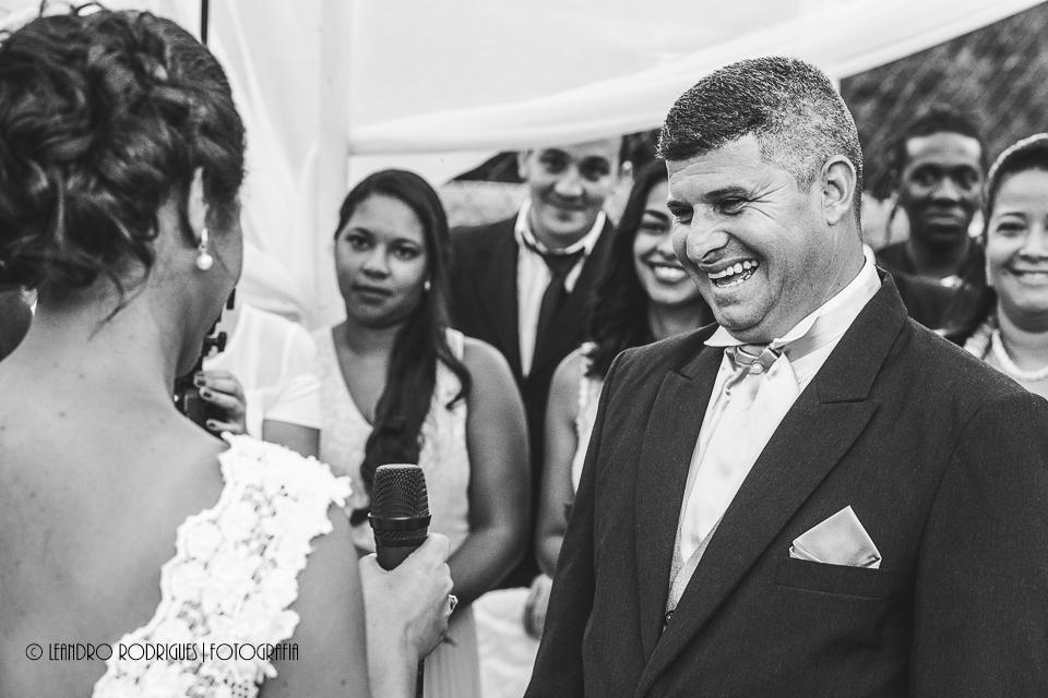 Noivo sorrindo ao escutar os votos da noiva