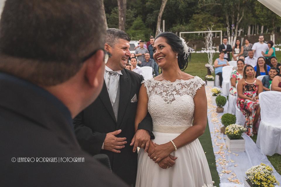 Noivo sorrindo e se olhando durante a cerimônia