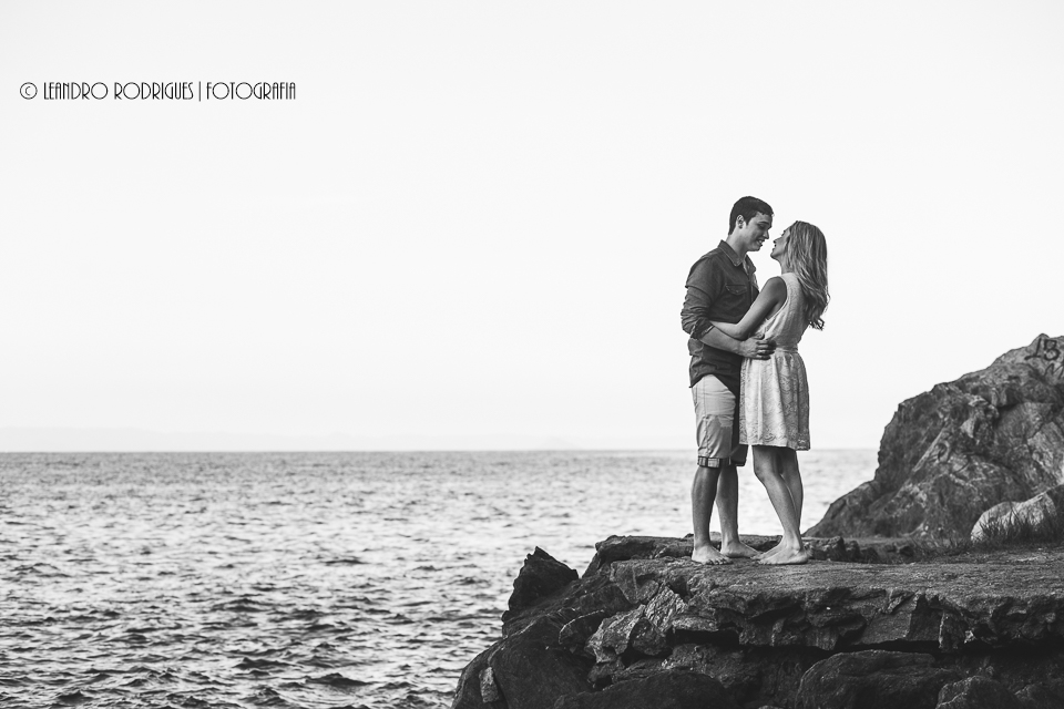 noivos um de frente paro outro, nas pedras da praia do Eden no Guarujá