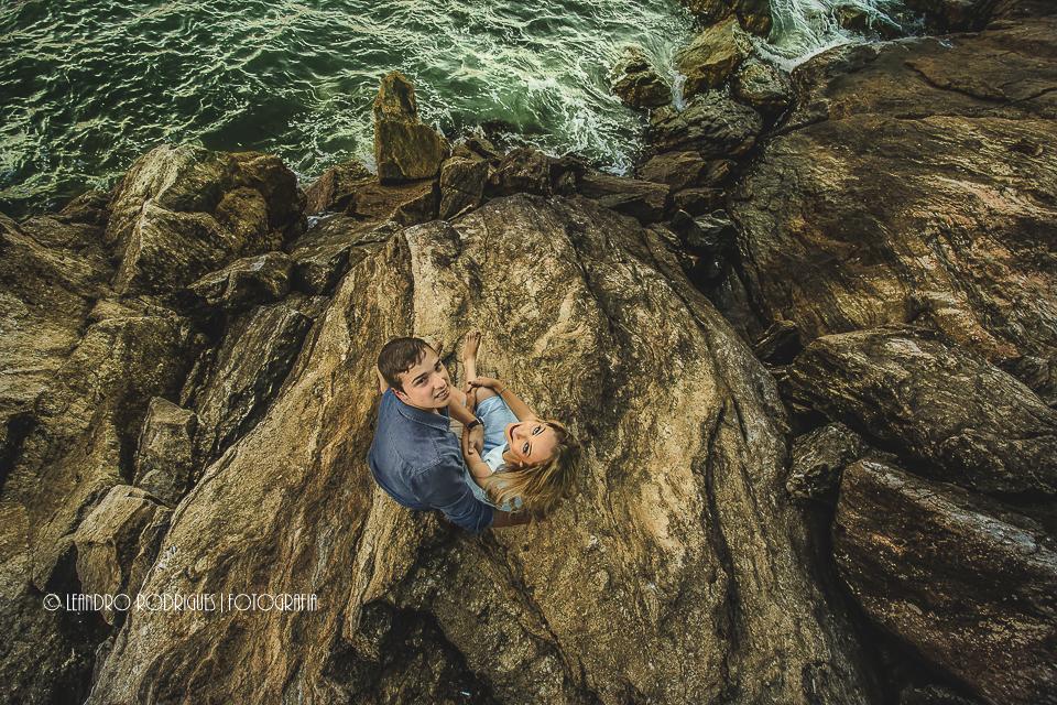 Noivos sentados na pedra olhando para cima