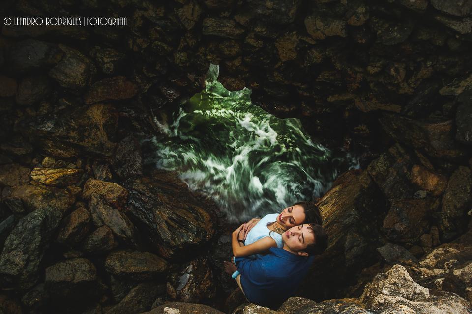 Noivos abraçados dentro de um buraco na praia do Eden no Guarujá