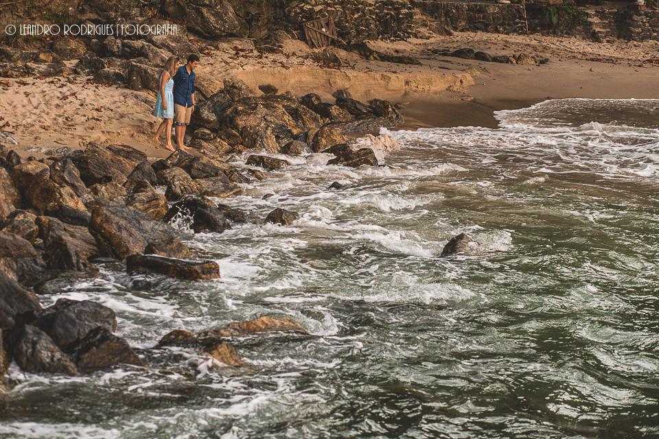 noivos olhando as ondas batendo nas pedras
