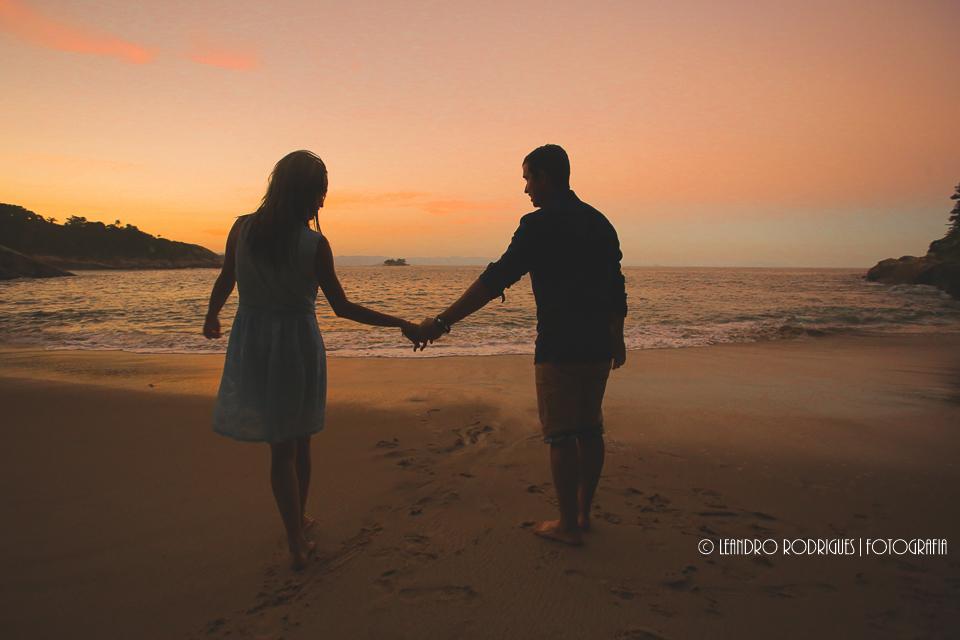 silhuetada dos noivos, de mão dadas ao por do sol