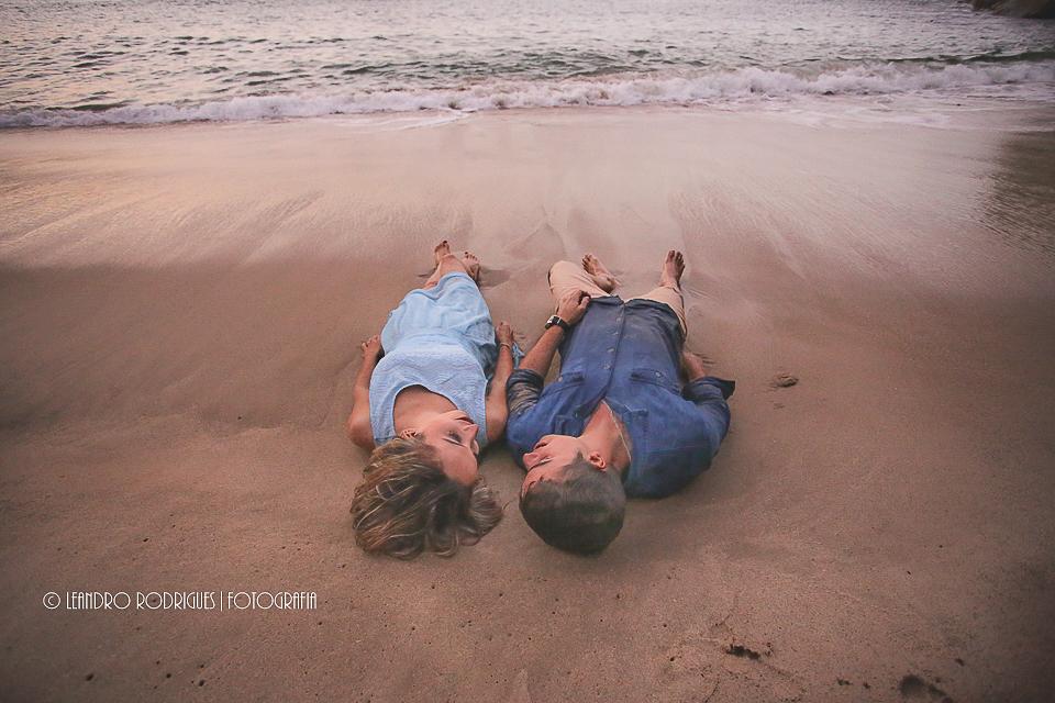 noivos deitados na beira da praia, no final de tarde ao por do sol