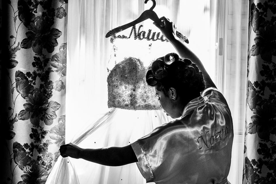 Noiva de frente para janela olhando o vestido, com cabide escrito noiva