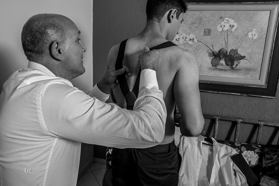Pai do noivo ajudando o noivo colocar suspensório