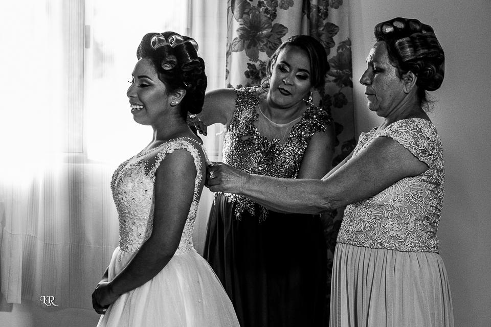 Mãe da noiva e sogra abotoando o vestido da nova