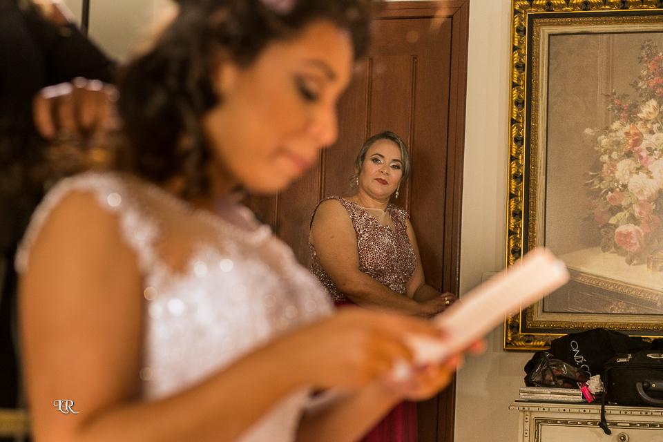 noiva sentada lendo a carta que o noivo enviou, e sogra olhando ela de fundo