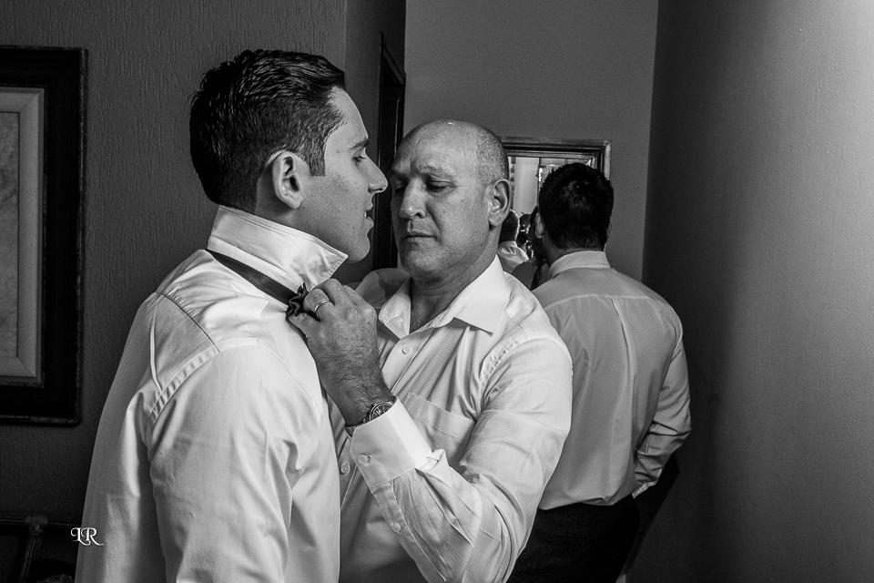 Pai do noivo abotoando a camisa do noivo e no fundo padrinho se arrumando de frente para o espelho