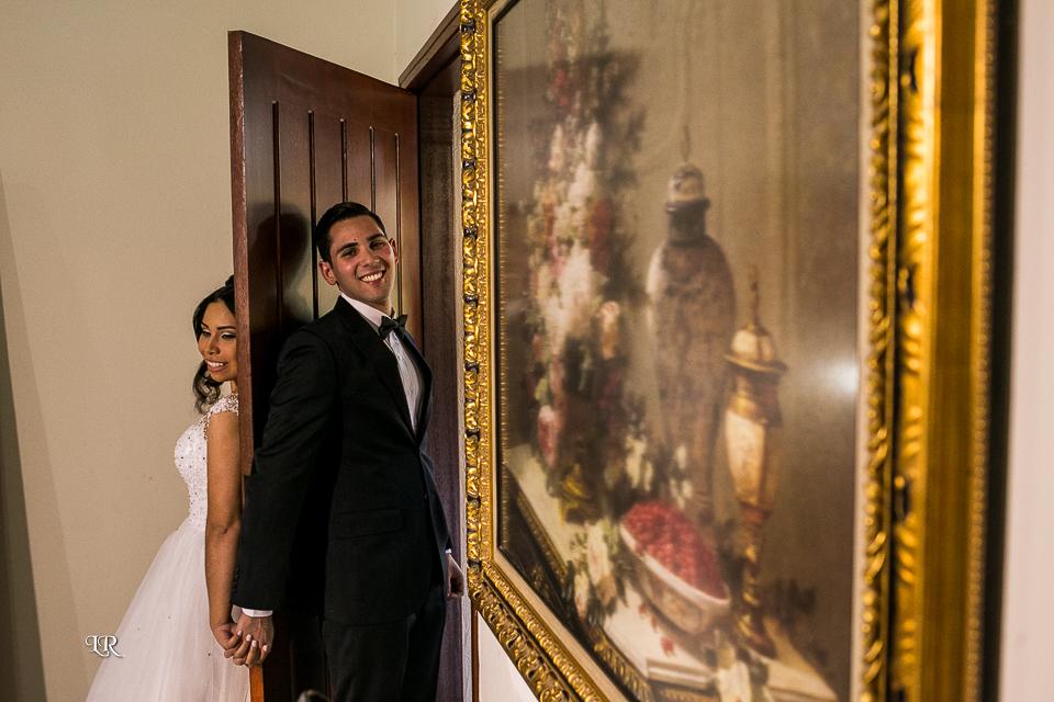 Noiva de um lado da porta e o noivo do outro de mãos dadas e do lado esquerdo um quadro na parede