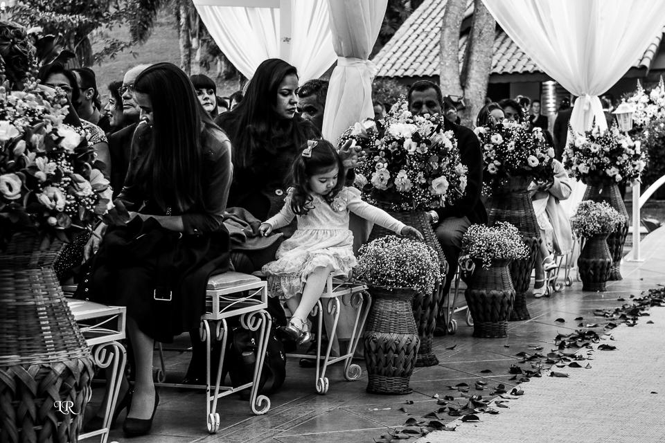 convidados sentados no lugar da cerimonia e criança passando a mão no arranjo de flores da decoração