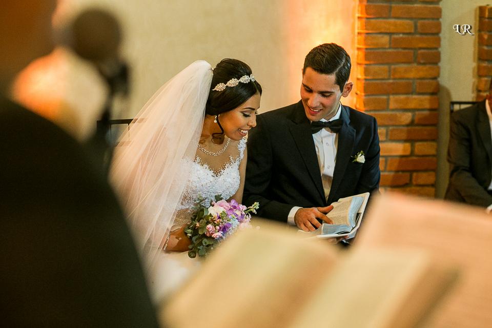 pastor celebrando a cerimonia e noivos sentados lendo a bíblia