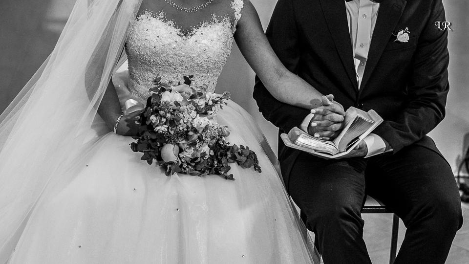 noiva segurando o buque com a mão esquerda e segurando a mão do noivo com a mão direita embaixo a bíblia