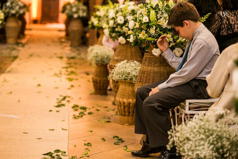 Criança sentada no local da cerimonia com a mão na flor