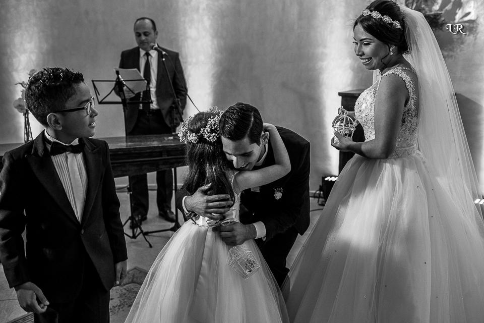 noivo abraçando a daminha de honra, noiva e noivinho olhando