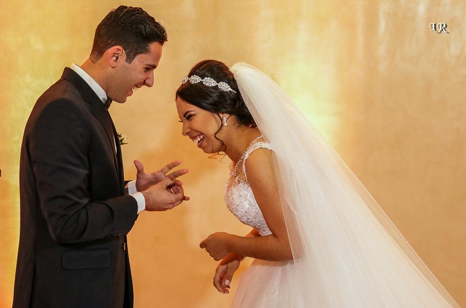 Noivo de frente da noiva tentando colocar aliança e noiva dando risada