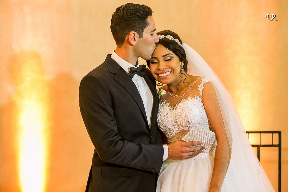 noivo do lado da noiva beijando a testa