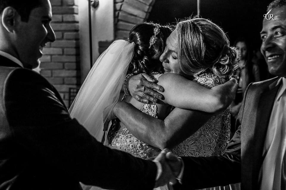 noiva abraçando a mãe e noivo cumprimentando o pai da noiva