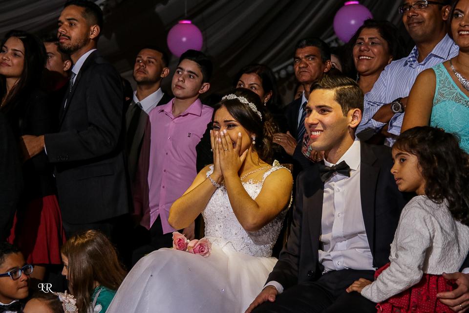 noivos assistindo a retrospectiva jundo com os convidados, noiva emocionada coma mão na boca