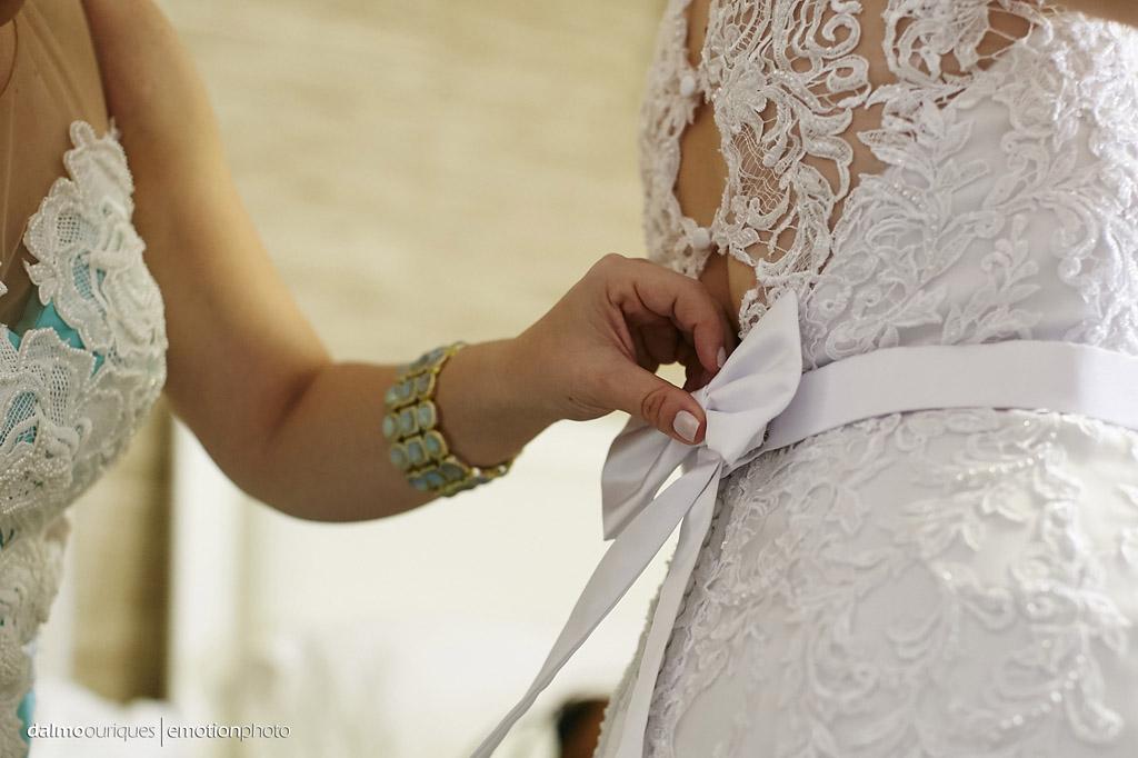 fotografo dalmo ouriques pega o detalhe do laço sendo colocando no vestido da noiva