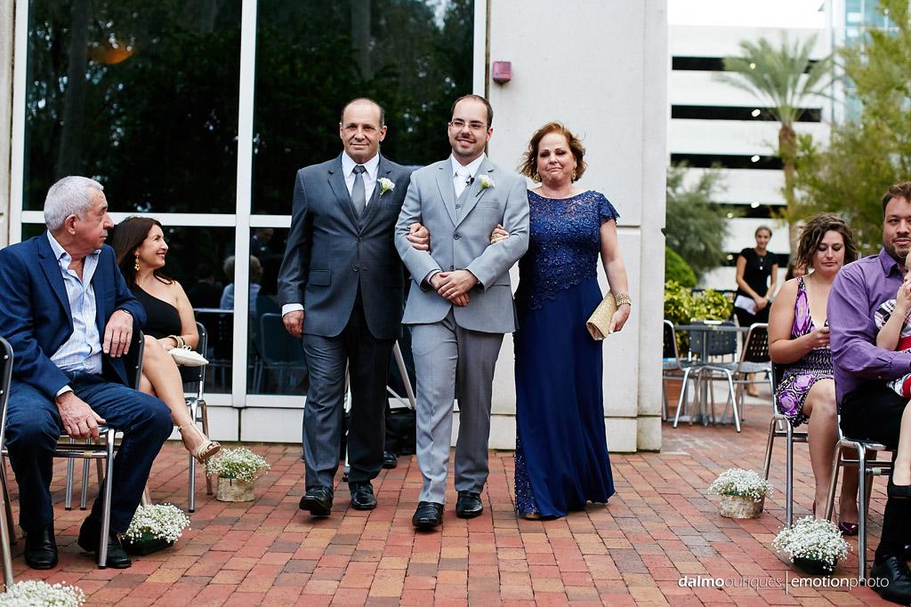 cerimonia do casamento em orlando começa com a entrada do noivo de braço com seus pais