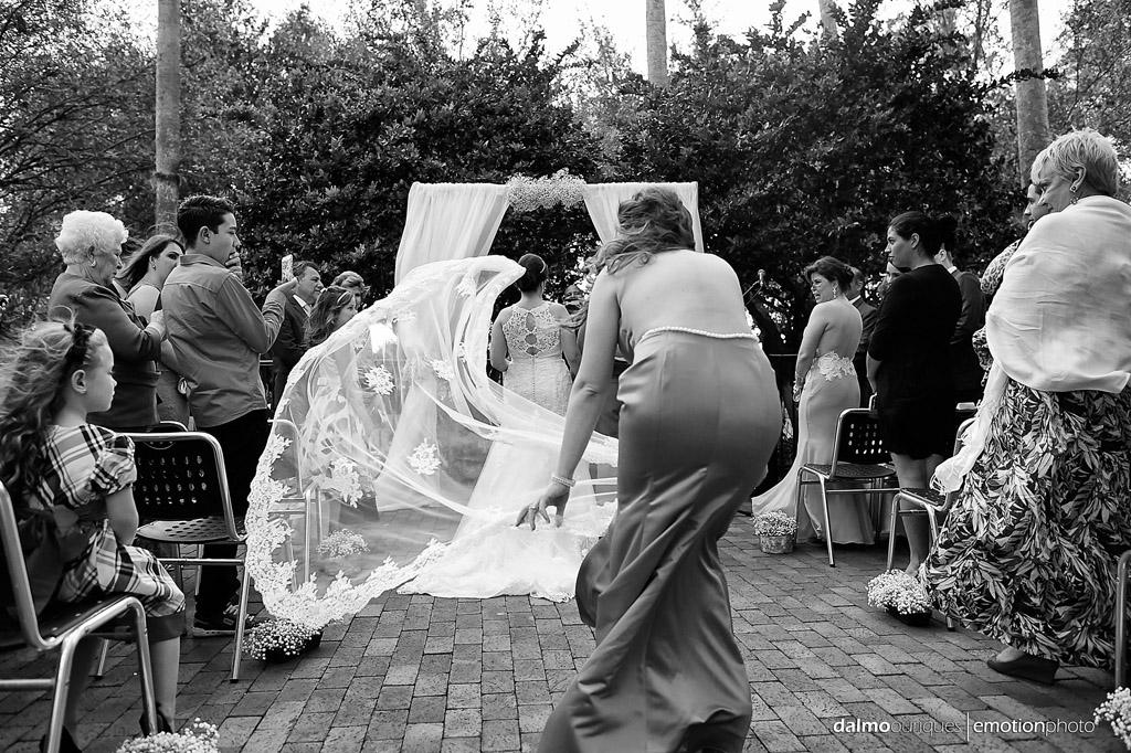 madrinha de casamento segura o véu da noiva, durante a cerimonia de casamento