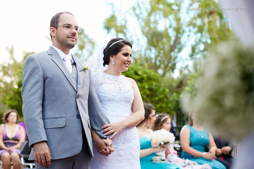 noivo usa um terno cinza e noiva um vestido de casamento branco