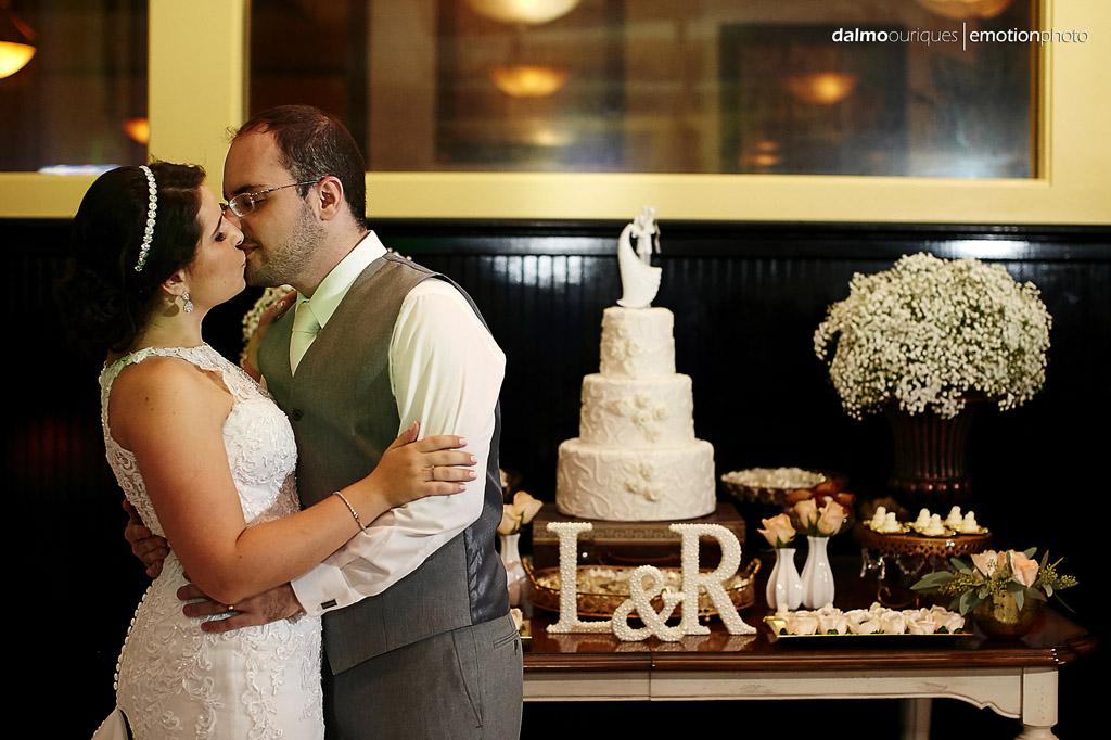 noivos se beijam na frente da mesa de doces e do bolo do casamento