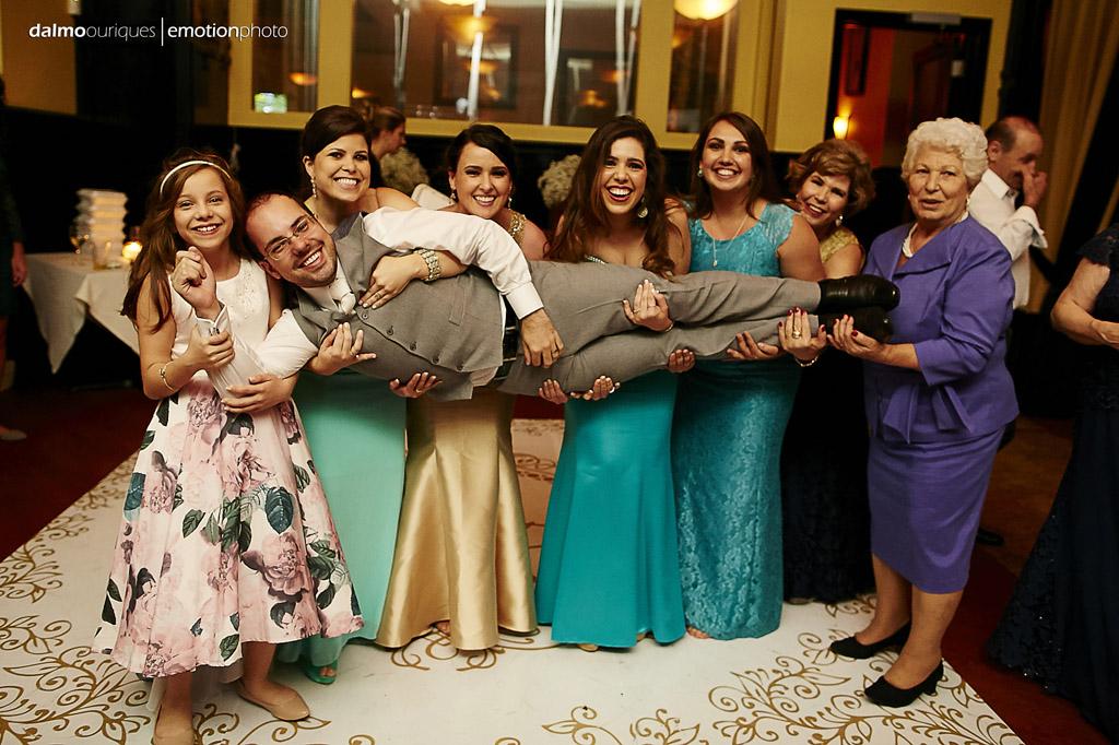 madrinhas do casamento pegam o noivo no colo, no final da festa de casamento