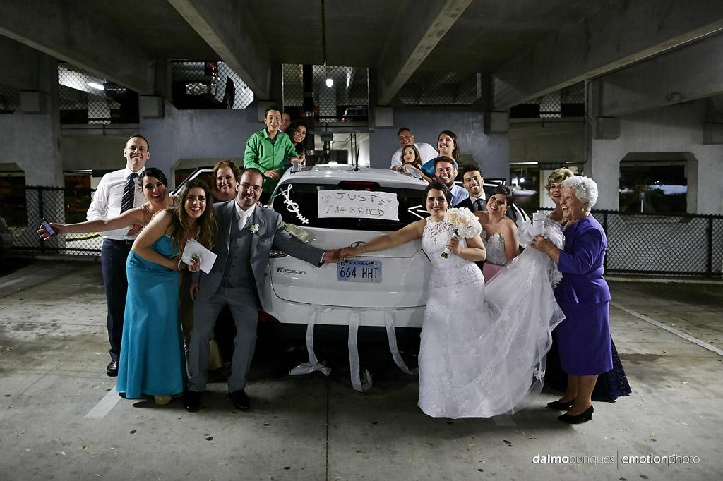 final de casamento com os noivos e convidados na frente do carro dos noivos
