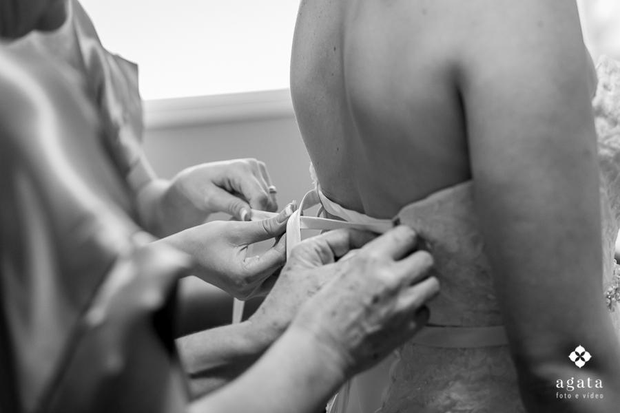 Mãe fechando o vestido da noiva