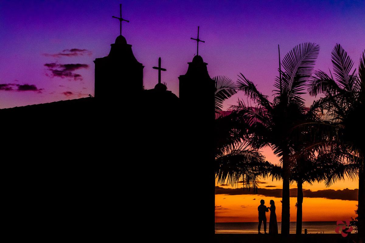 Silhueta dos noivos e da igreja ao entardecer