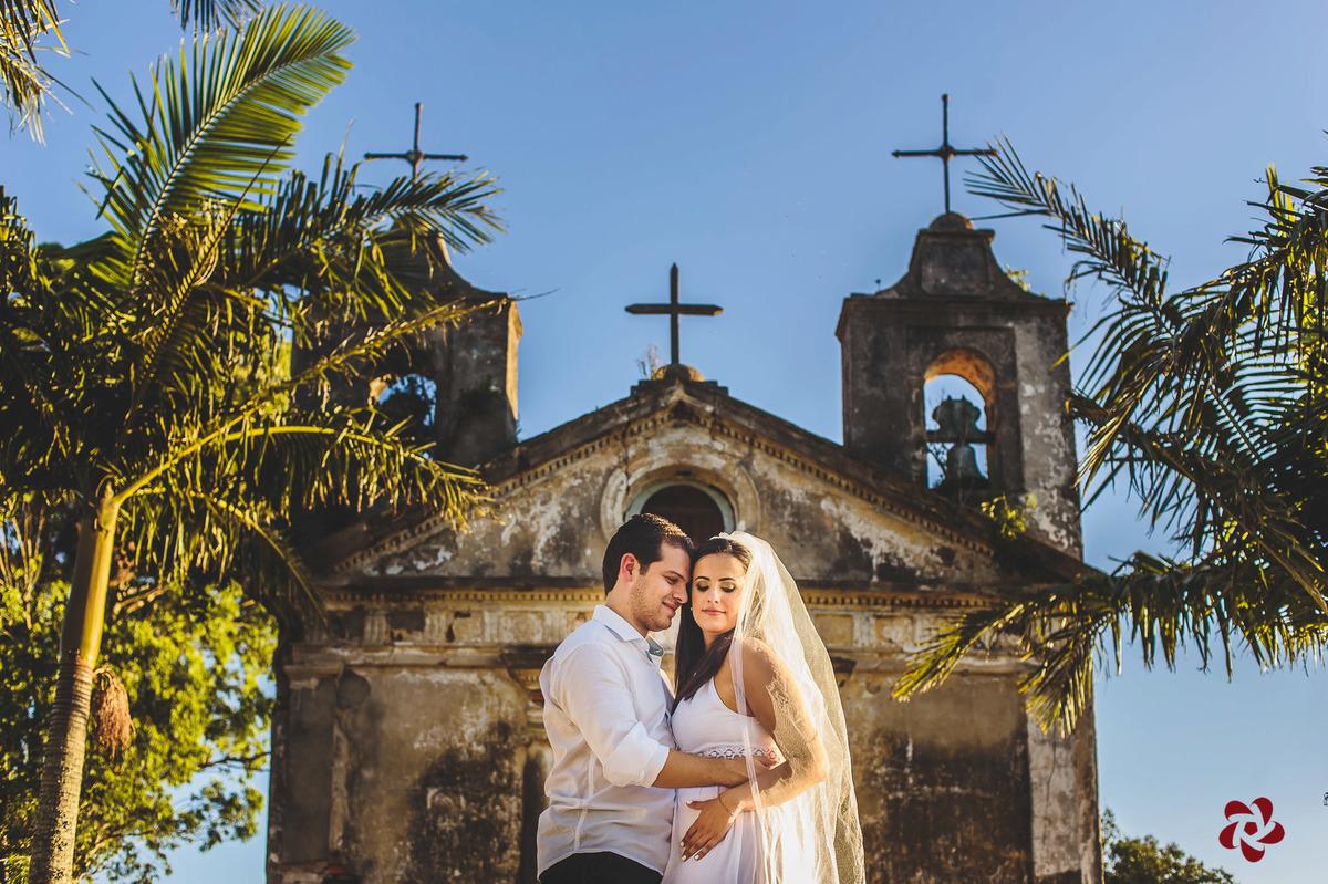 Noiva de véu e noivo olhando para ela