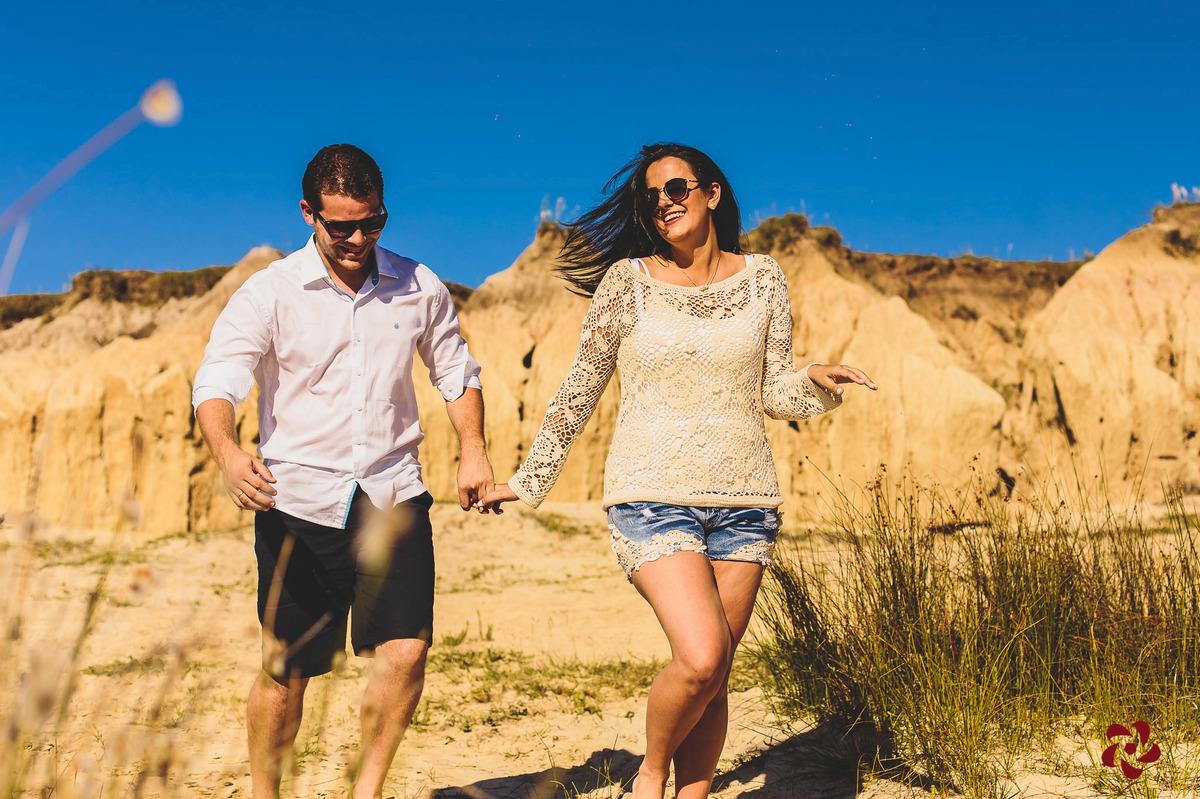 Noivos correndo de mãos dadas na areia