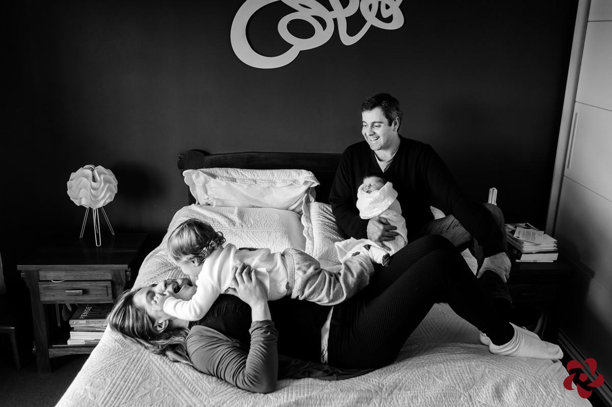 A família está no quarto, em cima da cama de casal em uma momento de interação e carinho.