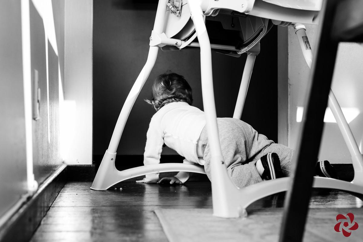 Otávio brinca de gatinhar embaixo da mesa entre as cadeiras.