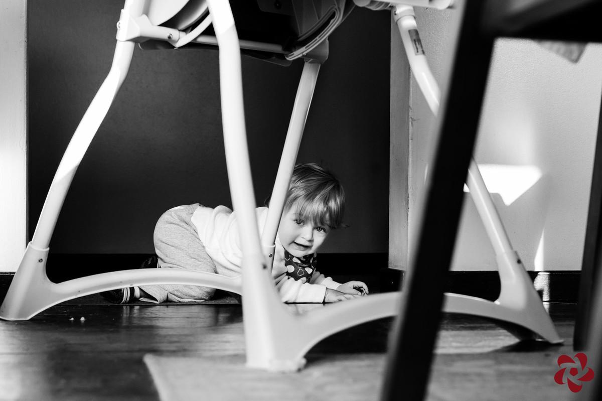 Enquanto Otávio brinca embaixo da mesa entre as cadeiras, engatinhando, ele olha para a câmera.