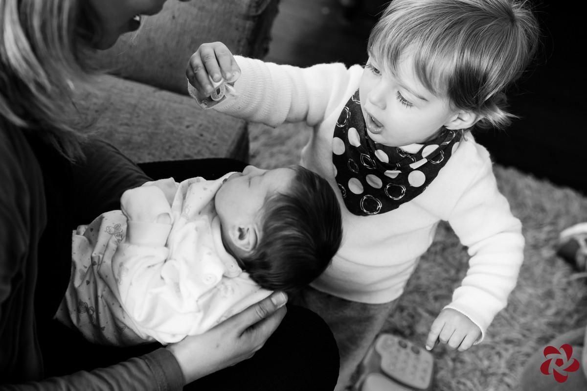 O irmão mais velho, Otávio, brinca de tirar a chupeta da irmã recém nascida, que está no colo da mãe.
