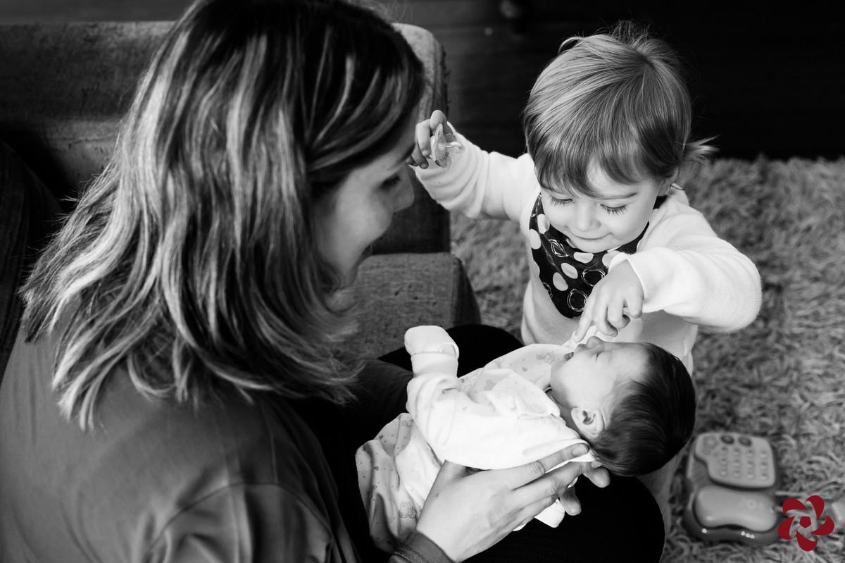 Júlia está no colo da sua mãe Natácia e Otávio, o irmão mais velho, brinca de encostar na sua boca e nariz.