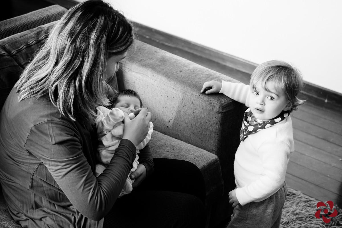 Natácia está sentada no sofá da sala com a Júlia no colo e Otávio, o filho mais velho, está ao lado olhando para a câmera.