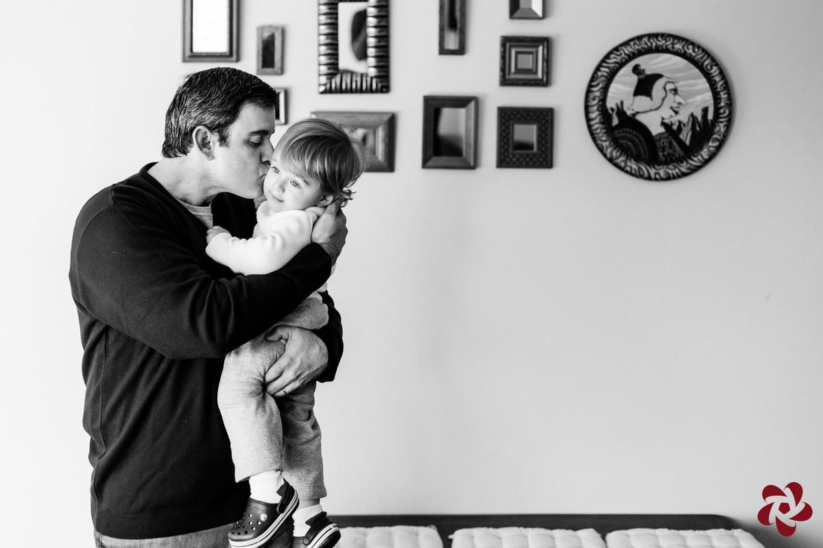 Rodrigo está com Otávio no colo, beijando seu rosto, em frente a uma parede decorada com quadros pequenos.