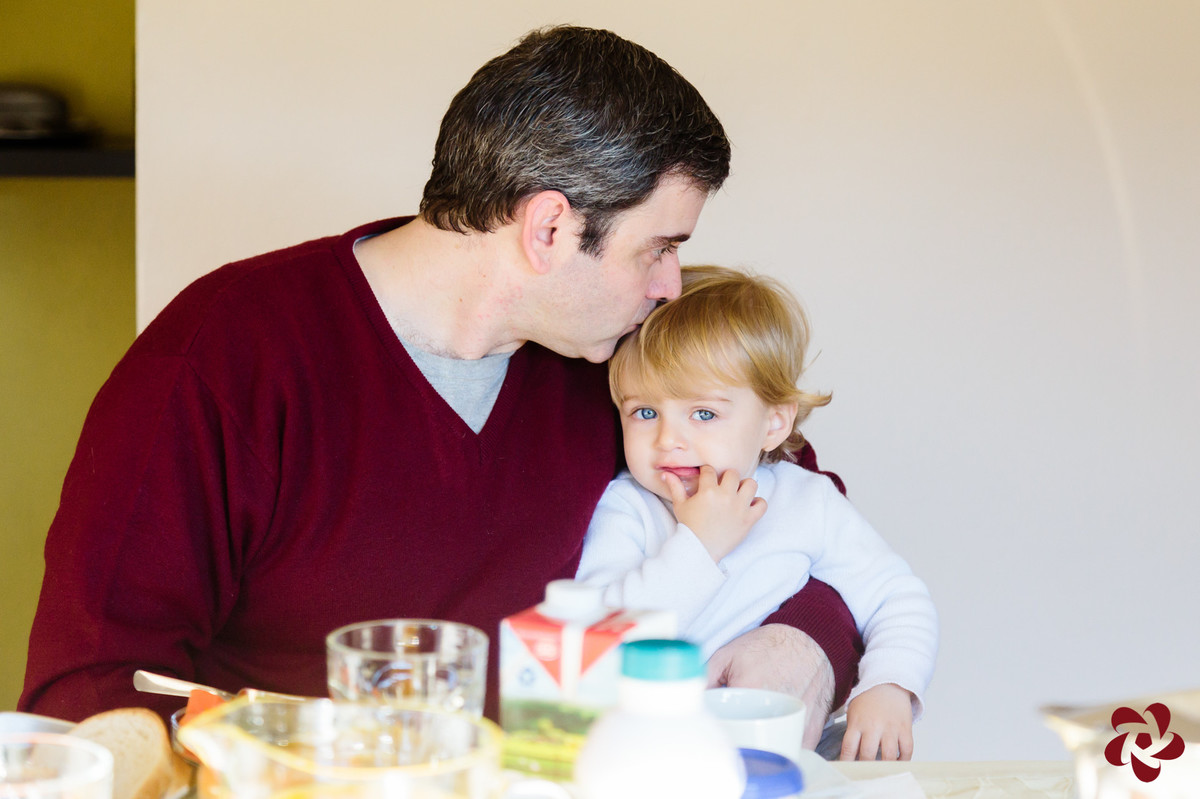 Otávio está sentado no colo do pai na mesa do café, olhando para a câmera com seus olhos azuis enquanto o pai lhe dá um beijo na cabeça.