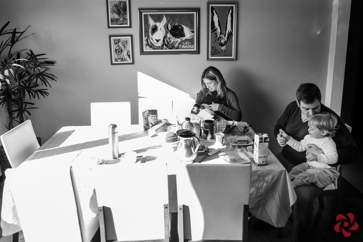 A família está reunida na mesa do café da manhã, a mãe está amamentando a filha e o pai está dando atenção ao filho mais velho