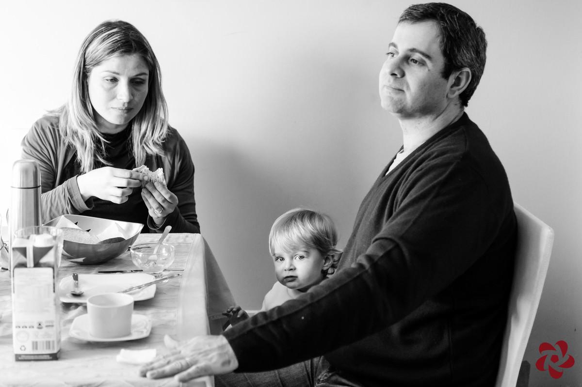 O casal está sentando na mesa de café da manhã e Otávio olha atentamente para a câmera.