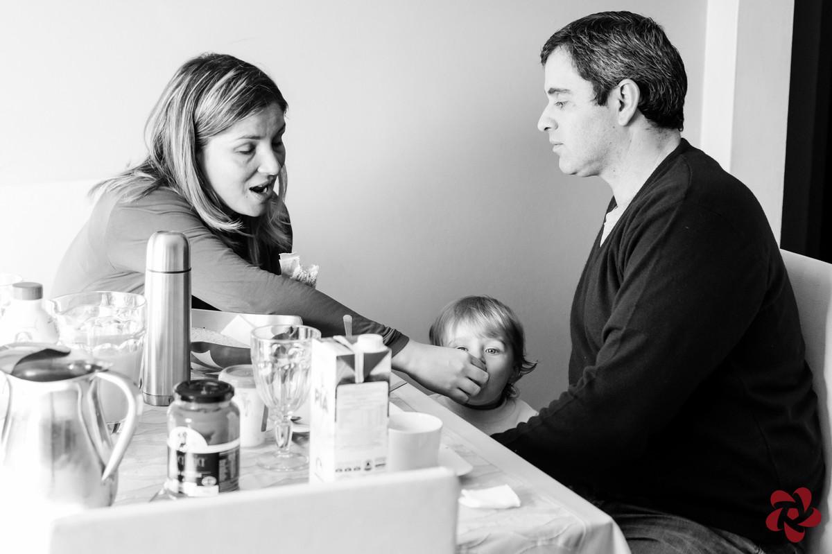 A mãe está dando pão na boca do filho que está parado ao lado do pai, na mesa do café da manhã de domingo.