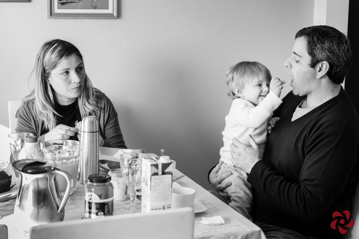 Otávio senta no colo do pai durante o café da manhã e lhe dá um pão na boca enquanto a mãe observa.