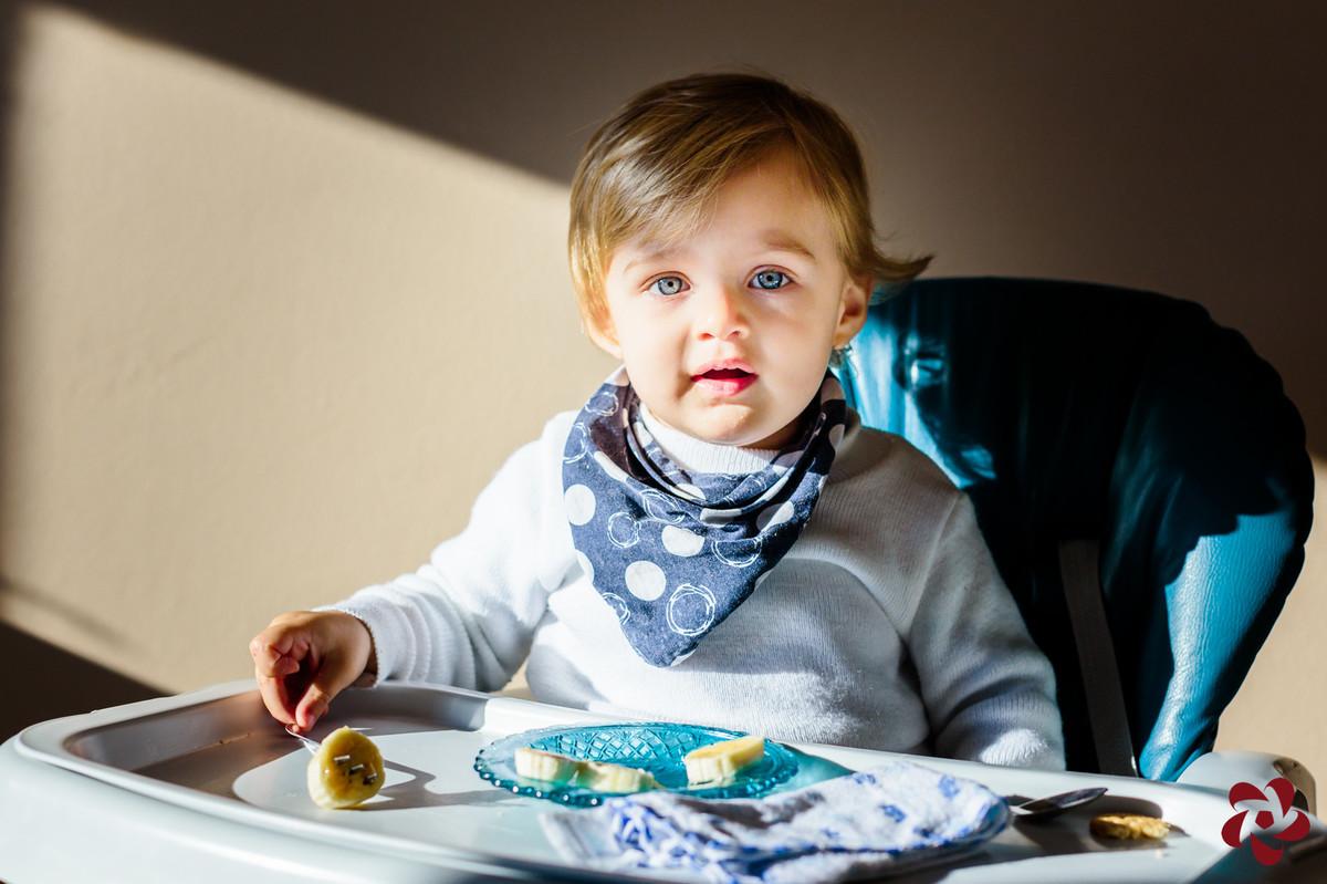 Otávio tem olhos azuis e está sentado no cadeirão comendo banana e olhando para a câmera.