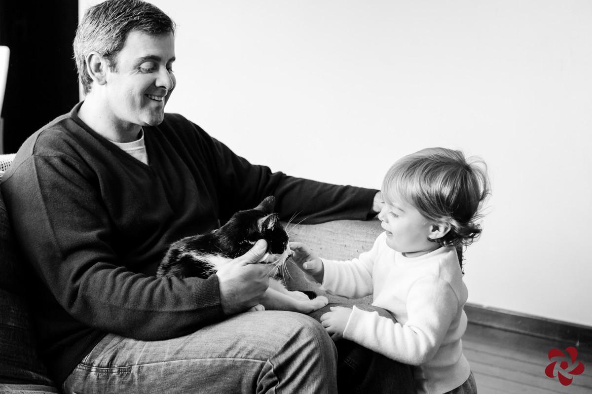 Rodrigo está no sofá com a gata no colo, que recebe a atenção do Otávio.