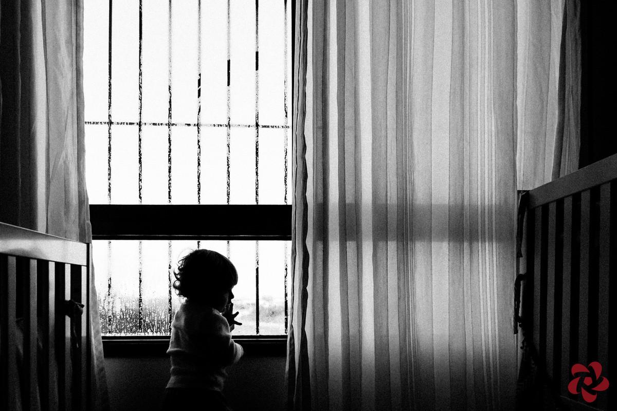 Em seu quarto, Otávio olha pela janela depois de brincar no vidro suado.